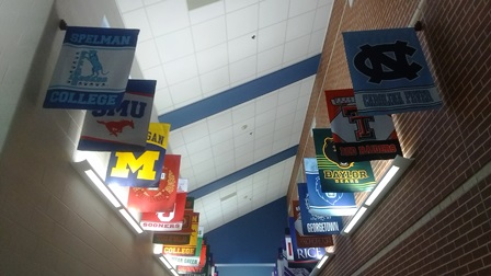 rows of college flags hanging from wall